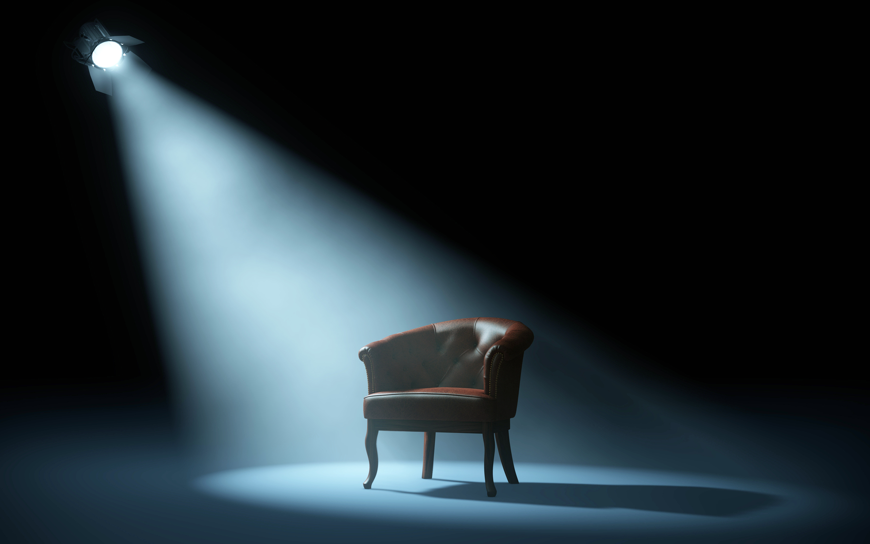 chair on stage under spotlight